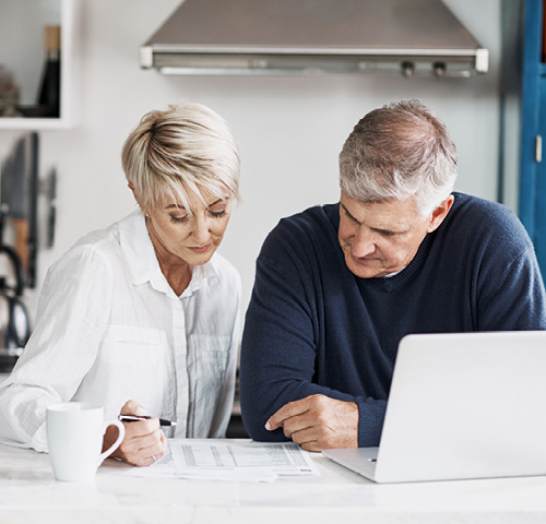 Elderly couple reviewing papers at home